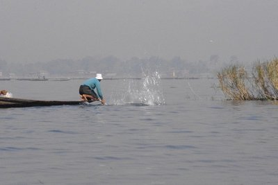 Scaring fish into nets with big sticks, whilst perched on the edge of a very thin boat