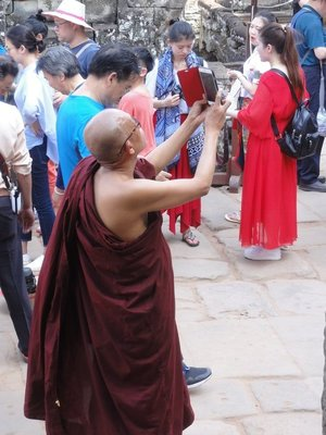 Monk visiting Bayon with modern technology
