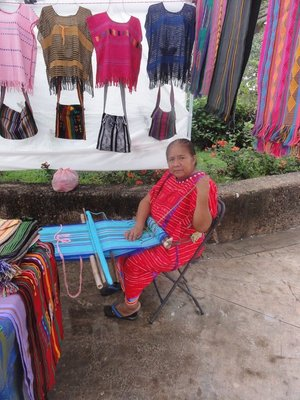 Woman weaving with a backstrap loom at the market