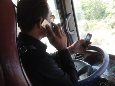 Our bus driver managing two cell phones and driving!!