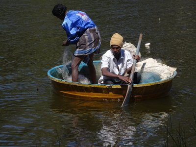 Fishermen on the lake in their round boat