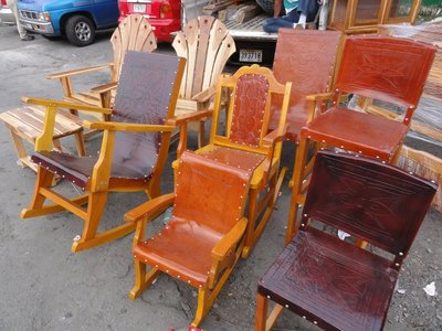 Beautiful wood and leather chairs being sold at the side of the street