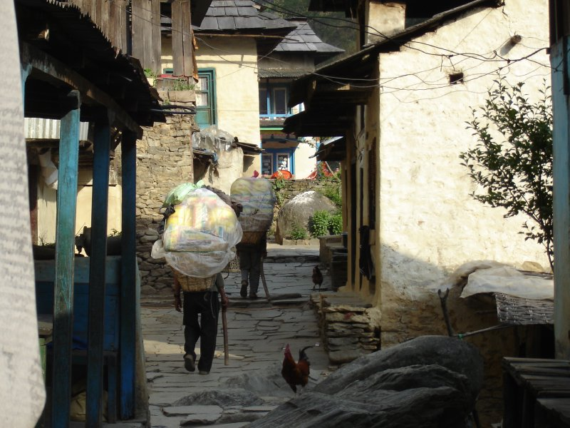 Above: Two porters make their way up the main street in Kinja. Porters seem to have been born into a life of purgatory but they go about their business with the minimum of fuss.