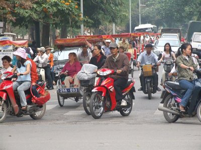 Foreigners on cyclos in the street of Hanoi