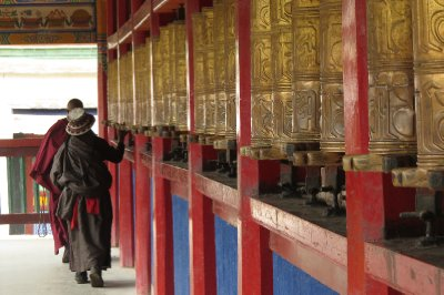 Monk and Tibetan women spinning prayer wheels