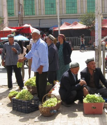 Uighur men selling grapes. Kashgar
