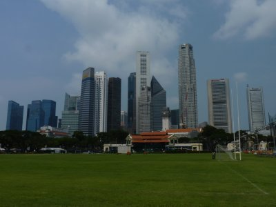 The old and new - Colonial era Cricket Club with football and rugby pitch, surrounded by the modern city skyscrappers
