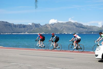 the common sight of (pretty fit) cyclists whizzing past the resort - Port de Pollenca in the background