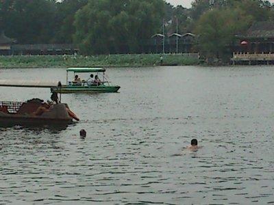 Old men swimming in dirty lake.