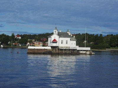 A HOUSE BUILT ON A ROCK IN THE MIDDLE OF THE FIORD