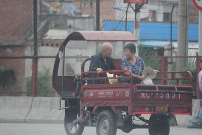 Grandparents taking a ride in a 3-wheel cart