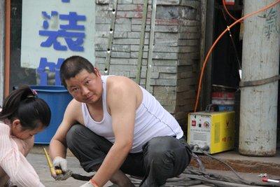 Daughter helping her father weld in Juizhaigou