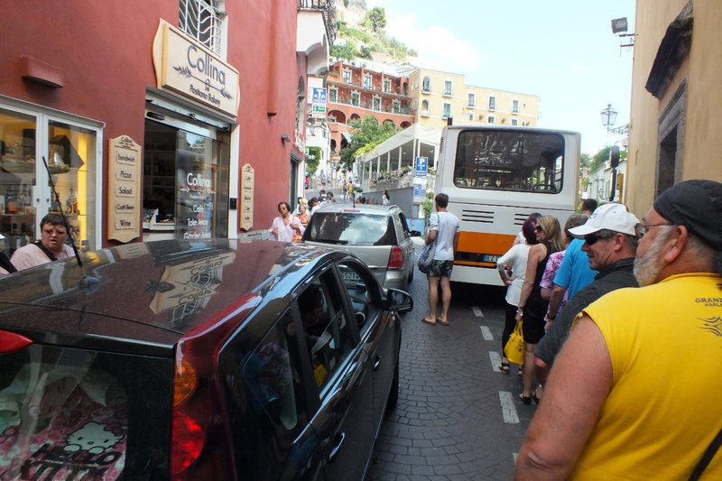 cars and pedestrians share the narrow roads