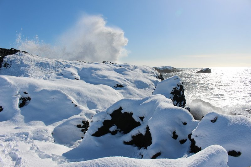 Waves breaking over snow covered rocks