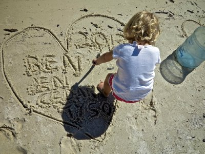Baby genius writing in the sand, next to conquor german