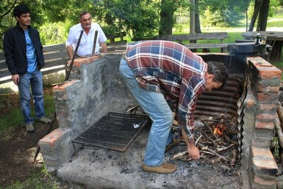Cliff starting the fire for the asado under the watchful eye of Hector.