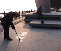 Old man's calligraphy in water at writer's square, Xiamen, China
