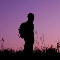stock-footage-man-with-backpack-walks-on-field-sunset-sky-in-background