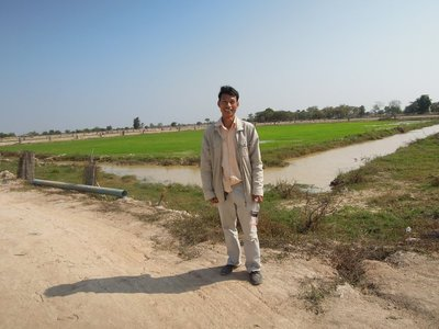 SATURDAY (12). This is SAVON - the supervisor in the ACODO school, standing in front of one of the rice fields/fish ponds. Rice in this field is close to harvest time. Harvest is staggered, so other rice fields are at different stages. So are the fish.