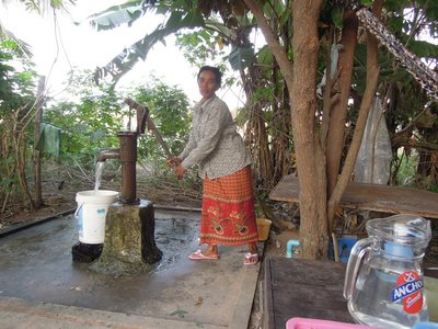 SATURDAY (12). A neighbour has come by to pump some water from the well that Kosal put in.