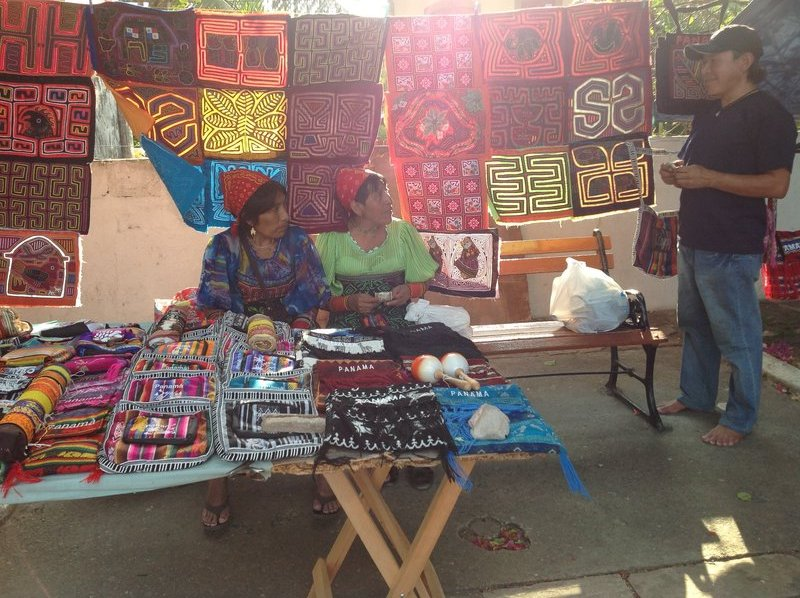 Molas are made by The Kuna women of Panama. The traditional dress of these women consists of a patterned skirt, red and yellow headscarf, arm and leg beads, gold  nose ring and earrings.