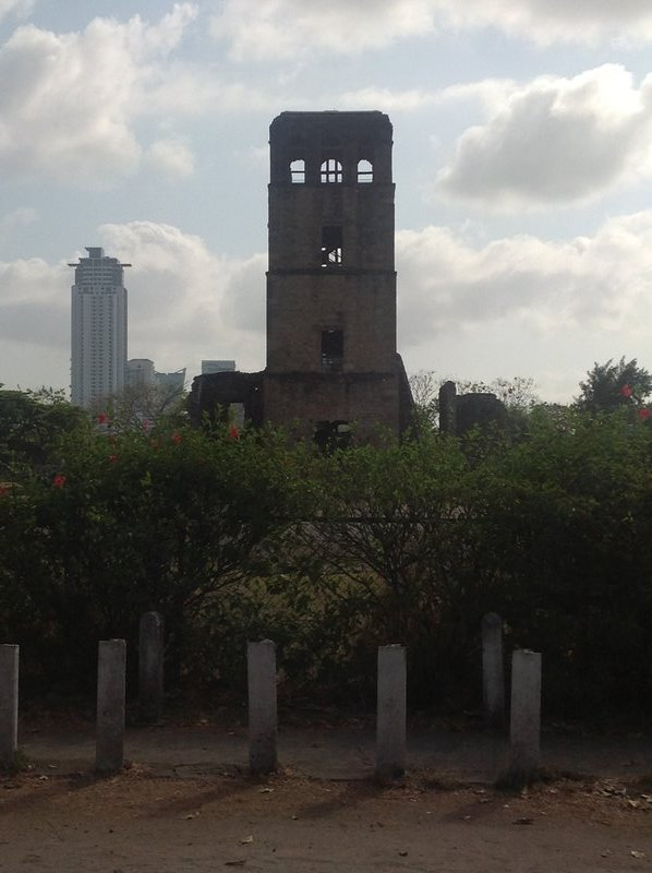 The bell tower of the Cathedral of Nuestra Señora de la Asunción at Panamá Viejo.  Not far away are skyscrapers of the modern city.