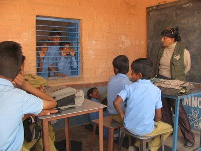 Parveen lectures to a small class of village school children