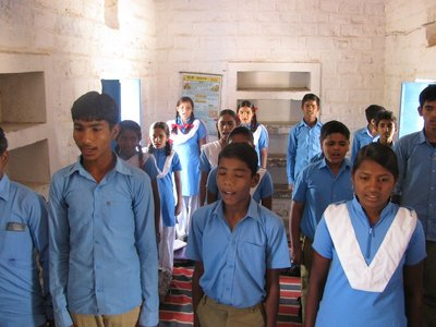 Village school children sing their national anthem to us