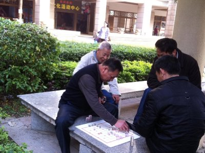 Retirees playing Chinese chess in a pavilion next to the play structure
