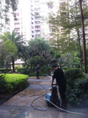 Men washing the walk paths with a moving spraying machine
