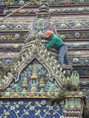 A worker cleans the Chinese porcelain decorations at Wat Arun.
