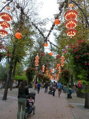 Illuminated pumpkin lanterns hanging above the path into Tivoli