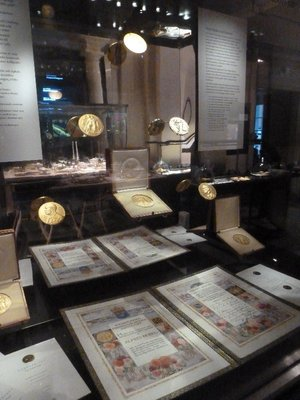 A display of the design of the 6 annual Nobel prizes - Physics, Chemistry, Medicine, Literature, Peace and 'Economics' - the latter is actually a prize awarded by the Bank of Sweden in memory of Alfred Nobel rather than  a Nobel prize itself