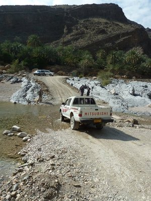 A Pickup Truck making its way across a ford in Wadi Shab