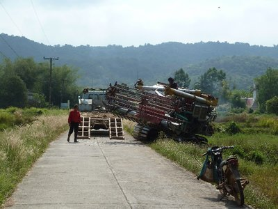 A local farmer unloading a rice harvester into his paddy fields
