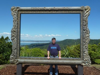 Me in a picture frame of the view of Manukau Harbour from Arataki