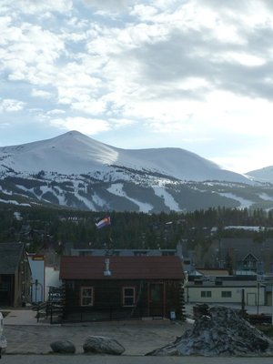 Mountain view over Breckenbridge with the Colorado Flag flying above a building in the foreground