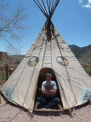 Me sitting cross-legged in the entrance of an Indian tepee