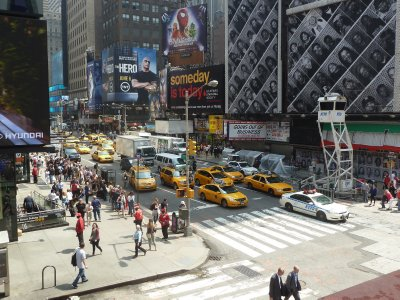 Looking down on 7th Avenue at Times Square, full of signature yellow NY cabs watched over by an unusual looking elevated police lookout post