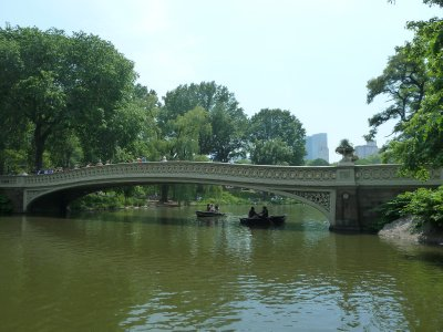 Boats going under a bridge across the Lake in Central Park
