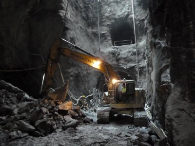The digger we viewed earlier from the surface at work in the tunnel