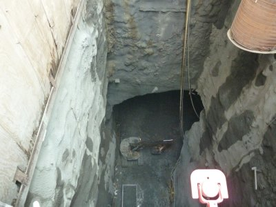 The view down from ground level of a digger at work in the subway tunnel 80 feet below