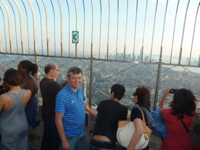 Me by the railings of the Observation Deck on the 86th floor with Lower Manhattan stretched out behind me