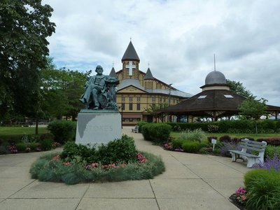 The statue of Ellwood H Stokes and the Great Auditorium at Ocean Grove