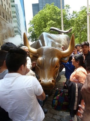 Tourists crowd around the Wall Street Bull