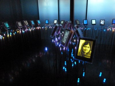 The darkened room of the 'Nobel Field' where iPads sway on the end of luminous rods with pictures of Nobel Prize winners; if touch one it gives details their peace citation, Malala Yousafzai for 2014 is in the foreground