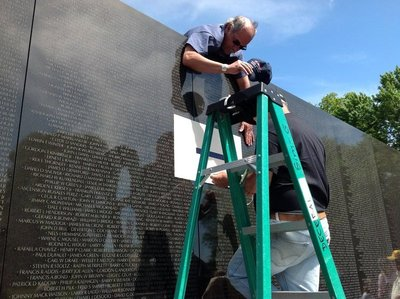 Workmen etching in new names on wall -after today there will be 58 286 names