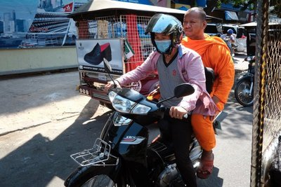 A monk catching a ride, Phnom Penh
