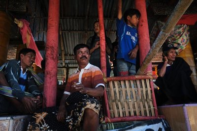 Men sit under the rice barns to watch the buffalo sacrifice