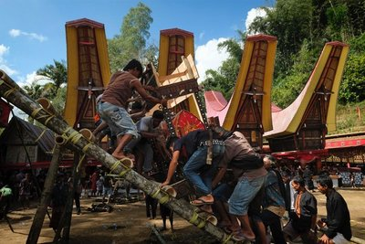 Heaving the coffin up a bamboo ladder to its temporary resting place